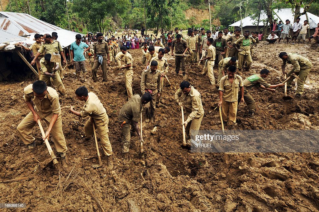 Indian paramilitary personnel dig through mud during a rescue operation after a landslide at Ujan Mudipara village in Baramura hills, 70 kms north of Agartala on May 9, 2013. Two bodies were recovered from the landslide. Cyclonic storms accompanied by lightning and rain continued to create havoc in Tripura for the fifth day, killing seven people, including five women and injuring 20 others, officials said AFP PHOTO/ STR