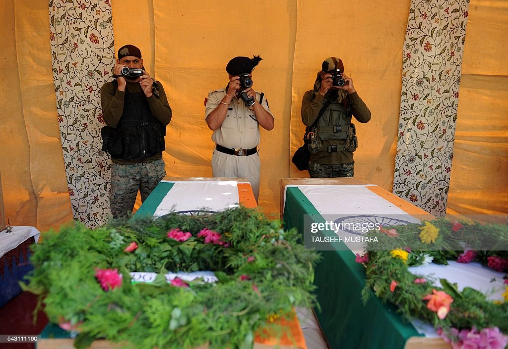 Indian paramilitary personnel photograph the coffins of colleagues killed in an ambush during a ceremony in Srinagar on June 26, 2016. At least eight Indian paramilitary soldiers and two suspected rebels were killed June 25 near Srinagar in India-administered Kashmir when a group of armed militants ambushed the soldiers' convoy, police said. Four militants sprayed bullets on the convoy carrying members of India's Central Reserve Police Force (CRPF) near Pampore town, killing five soldiers instantly and wounding 20, inspector general of police for the region, Javaid Gillani, told AFP. / AFP / TAUSEEF