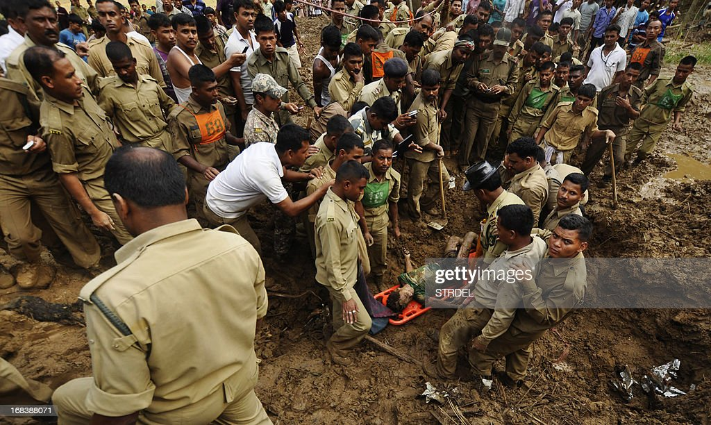 Indian paramilitary personnel put the body of a young boy found in the mud on a stretcher during a rescue operation after a landslide at Ujan Mudipara village in Baramura hills, 70 kms north of Agartala on May 9, 2013. Two bodies were recovered from the landslide. Cyclonic storms accompanied by lightning and rain continued to create havoc in Tripura for the fifth day, killing seven people, including five women and injuring 20 others, officials said