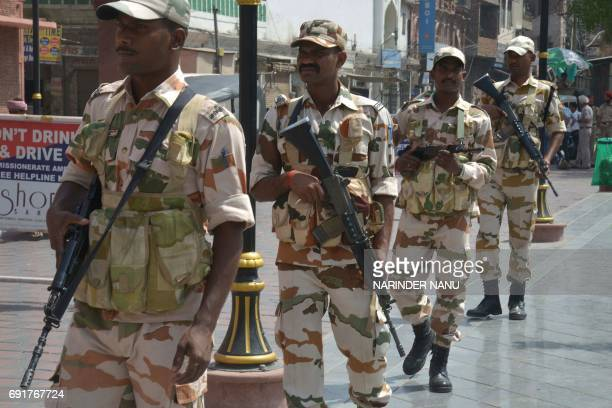 Indian paramilitary personnel walk through a market area of Amritsar on June 3 as security is increased ahead of the anniversary of Operation Blue...
