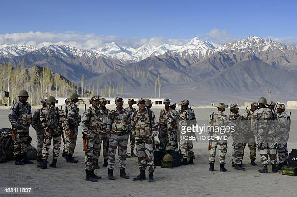 Indian paramilitary police wait as election workers receive polling materials including Electronic Voting Machines at a temporary election office on...