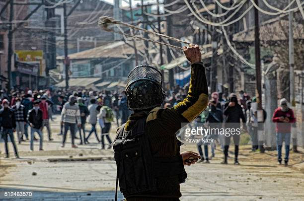 Indian paramilitary soldier throws a stone at Kashmiri Muslim protesters with his sling shot during an anti India protest on February 26 2016 in...