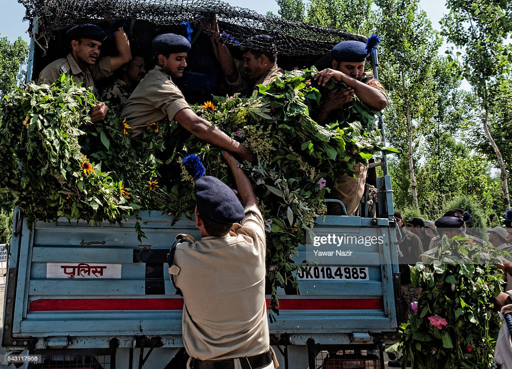 Indian Paramilitary soldiers of Central Reserve Police Force (CRPF) carry wreaths to lay them on the coffins containing bodies of their killed comrades during a wreath-laying ceremony of eight CRPF soldiers killed in an ambush on June 26, 2016 in Srinagar, the summer capital of Indian Administered Kashmir, Indian. Eight Indian Central Reserve Police Force troopers were killed and another twenty critically wounded on Saturday after pro freedom rebels ambushed a paramilitary convoy on the Srinagar-Jammu highway near Pampore in Jammu and Kashmir's Pulwom district, police said. The firing was returned and two rebels were killed in the retaliatory action by the CRPF troopers. A wreath-laying ceremony was held today by the CRPF for their killed comrades.