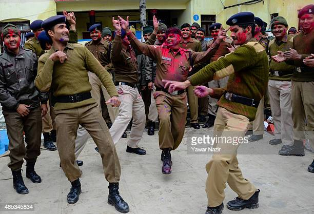Indian Paramilitary soldiers of the Central Reserve Police Force smeared in colour dance at their camp during Holi celebrations at a camp of the...