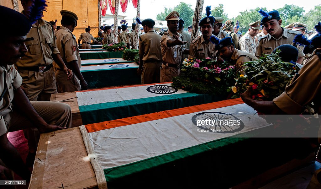Indian Paramilitary soldiers of the Central Reserve Police Force (CRPF) lay wreaths on the coffins containing bodies of their killed comrades during a wreath-laying ceremony of eight CRPF soldiers killed in an ambush on June 26, 2016 in Srinagar, the summer capital of Indian Administered Kashmir, Indian. Eight Indian Central Reserve Police Force troopers were killed and another twenty critically wounded on Saturday after pro freedom rebels ambushed a paramilitary convoy on the Srinagar-Jammu highway near Pampore in Jammu and Kashmir's Pulwom district, police said. The firing was returned and two rebels were killed in the retaliatory action by the CRPF troopers. A wreath-laying ceremony was held today by the CRPF for their killed comrades.