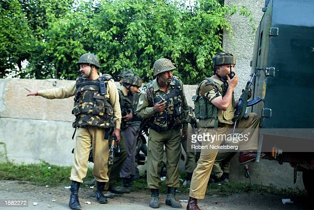 Indian paramilitary soldiers one of them holding a dead militants' AK47 gun regroup following the detonation of a large explosive device inside a...