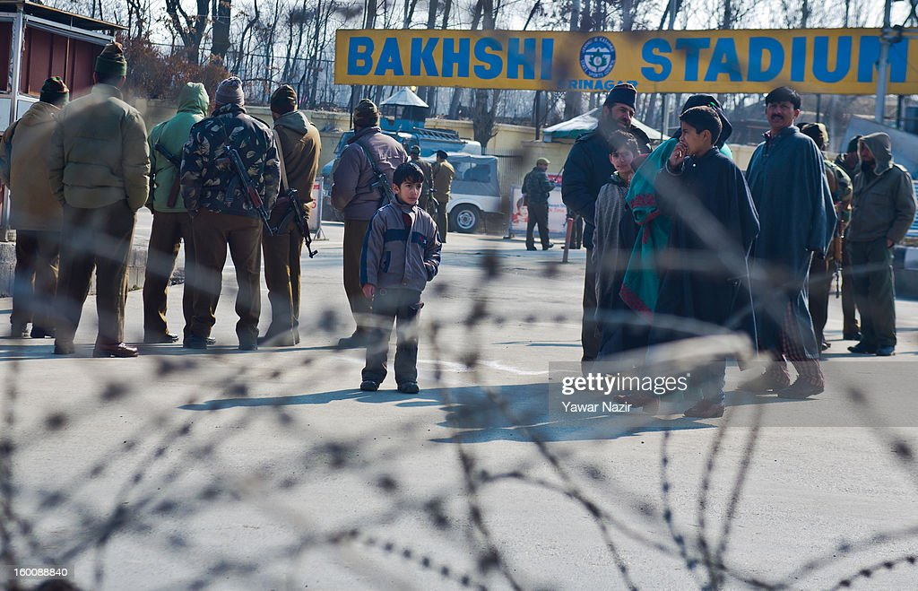 Indian paramilitary soldiers stand guard as Kashmiri children look towards them outside the Bakshi stadium , where the authorities hold the main function city during India's Republic Day celebrations on January 26, 2013 in Srinagar, the summer capital of Indian Administered Kashmir. All businesses, schools and shops were closed and traffic remained off the roads following a strike call given by Kashmiri separatist leaders against India's Republic Day celebrations in Kashmir. Meanwhile India deployed large numbers of Indian police and paramilitary forces to prevent any incidents during the official celebrations.