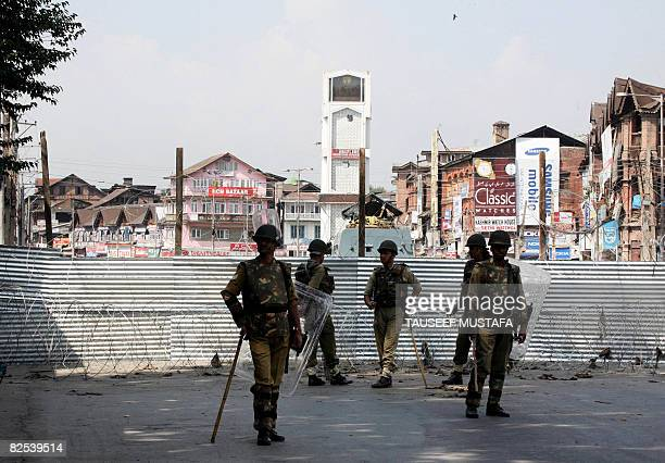Indian paramilitary soldiers stand guard by a barricade erected at the proposed venue of an independence rally at Lal Chowk in Srinagar on August 25...
