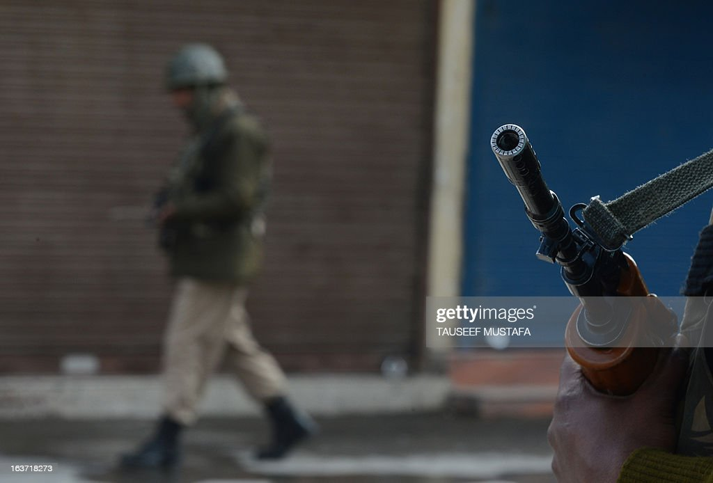 Indian Paramilitary soldiers stand guard during the second day of curfew, imposed on the Kashmiri summer capital in Srinagar on March 15, 2013. Indian-administered Kashmir's main city was under curfew after the killing of five paramilitary police and the death of two civilians cranked up tensions in the disputed region. Kashmir's inspector general of police Abdul Gani Mir said a round-the-clock curfew order had been imposed in the city of Srinagar while there were similar restrictions in other towns and villages in the Kashmir Valley. AFP PHOTO/ Tauseef MUSTAFA