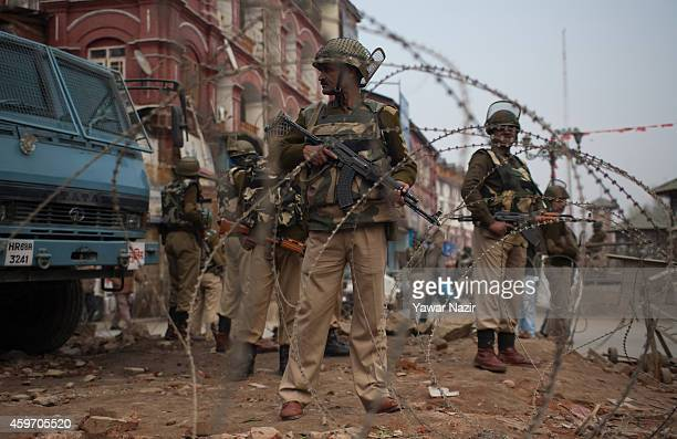 Indian paramilitary soldiers stand guard near their bunker next to the spot where a grenade attack took place in the city centre on November 29 in...