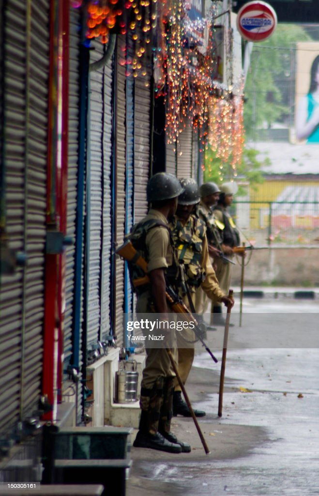 Indian paramilitary soldiers stand guard next to the closed shops decorated overnight by the supporters of political parties in the main city during India's Independence Day celebrations on August 15, 2012 in Srinagar, the summer capital of Indian Administered Kashmir. All businesses, schools and shops were closed and traffic remained off the roads following a strike call given by Kashmiri separatist leaders against India's Independence Day celebrations in Kashmir. Meanwhile India deployed large numbers of Indian police and paramilitary forces to prevent any incidents during the official celebrations.