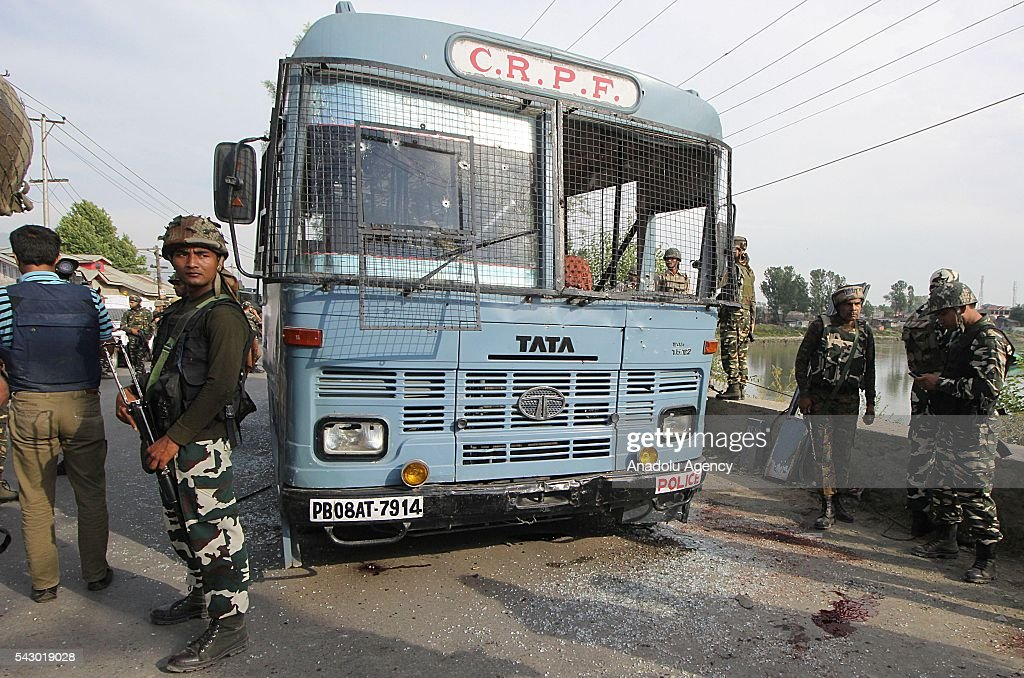 Indian paramilitary soldiers stand near the damaged vehicle which was attacked by suspected militants in Pampore, on the outskirts of Srinagar, the summer capital of Indian controlled Kashmir on June 25, 2016. Eight Indian paramilitary soldiers were killed and other 20 were injured in the shootout. Later police said two unidentified militants were also killed where the shootout took place.