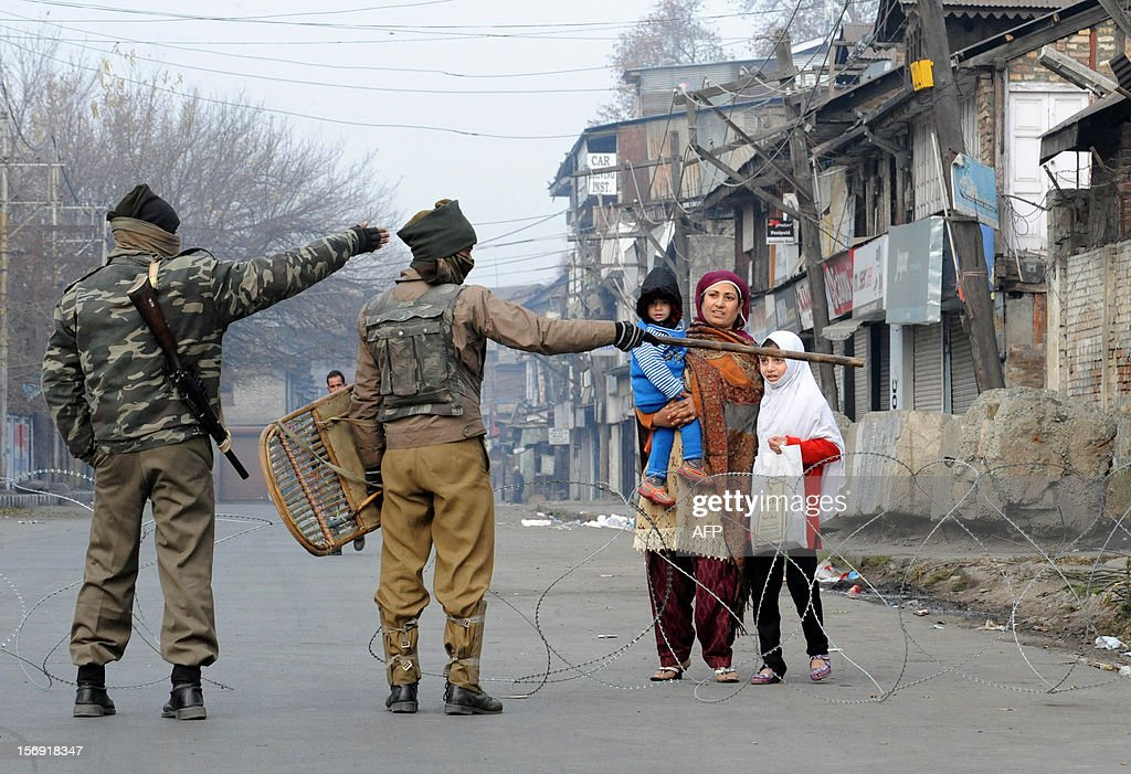 Indian paramilitary soldiers stop a Kashmiri family on a deserted street during restrictions on a Muharram procession in Srinagar on November 25, 2012. Authorities imposed restrictions in parts of Srinagar, the summer capital of Kashmir, to thwart planned Muharram processions. AFP PHOTO/Rouf BHAT