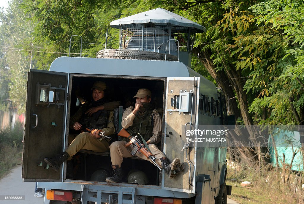 Indian paramilitary trooper ride inside a vehicle on the outskirts of Srinagar on October 3, 2013, following an encounter with suspected militants in the restive state. Four policemen were injured in a late-night encounter on the outskirts of Srinagar, as suspected militants who were hiding inside a house escaped under the cover of darkness police officials said. AFP PHOTO/Tauseef MUSTAFA