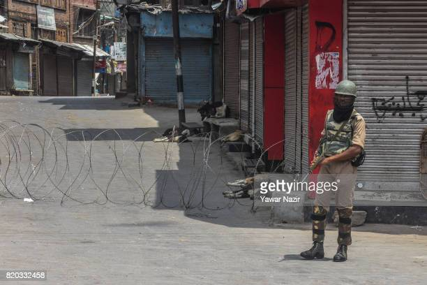 Indian paramilitary trooper stands guard as stray dogs rest in front the shuttered shops in the old city during curfew on July 21 2017 in Srinagar...