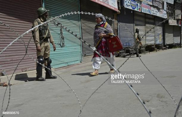 Indian paramilitary trooper stands guard by a barbed fence wire as a Kashmiri woman walks past during a curfew in central Srinagar on May 29 2017...