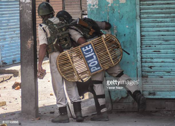 Indian paramilitary troopers look towards Kashmiri Muslim protester throwing stones at them during a protest after Kashmiri Muslims defied curfew on...