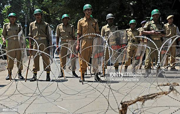 Indian paramilitary troopers stand guard as supporters of the ruling National Conference shout slogans during a protest against Kashmir's main...