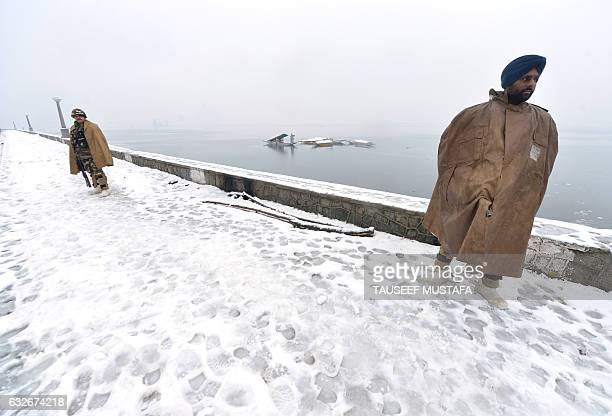 Indian paramilitary troopers stand guard on the shores of Dal Lake during a snowfall in Srinagar on January 25 2017 Security has been beefed in...