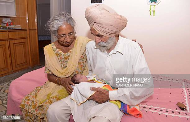 Indian parents Mohinder Singh Gill and Daljinder Kaur pose for a photograph as they hold their newborn baby boy Arman at their home in Amritsar on...
