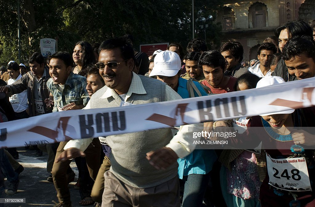 Indian participants including transgenders, drug users, sex workers and people living with HIV, break the tape at the start of the All-India Run as they observe World Aids Day in New Delhi on December 2, 2012. More than 1,000 people joined together to raise awareness of the continued support needed to address HIV among high-risk groups and to celebrate the diversity of affected communities. AFP PHOTO/ Anna ZIEMINSKI