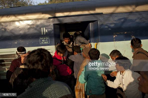 Indian passengers rush to board a train pulling onto the platform at the Hazrat Nizamuddin railway station in New Delhi on February 26 when the...