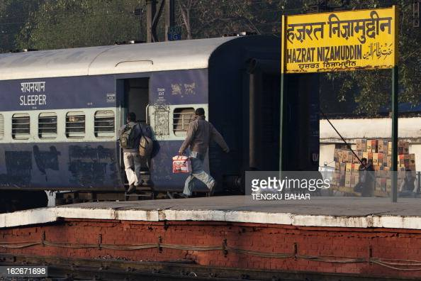 Indian passengers rush to board the last compartment of a departing train at the Hazrat Nizamuddin railway station in New Delhi on February 26 when...