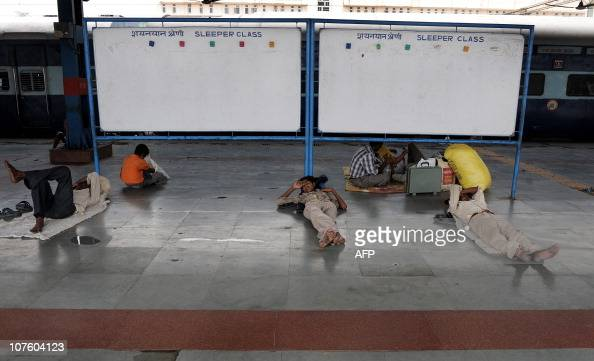 Indian passengers take a nap as they wait for their train at the New Delhi Railway Station in New Delhi on July 3 2009 Railways Minister Mamata...