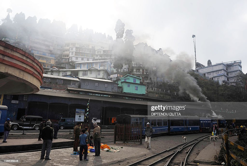 Indian passengers wait for a steam engine train, locally known as the toy train, in Darjeeling on December 22, 2012. The economy of the eastern Indian state of Sikkim is being buoyed by the ever increasing numbers of foreign and domestic tourists keen to view the mountains of the Himalayan mountain range. AFP PHOTO/ Diptendu DUTTA