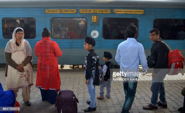 Indian passengers wait for a train as they stand on a platform alongside carriages of The Swarn Shatabdi Express at the railway station in Amritsar...
