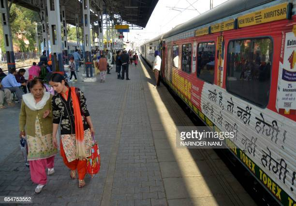 Indian passengers wait for a train as they walk on a platform alongside carriages of The Swarn Shatabdi Express at the railway station in Amritsar on...