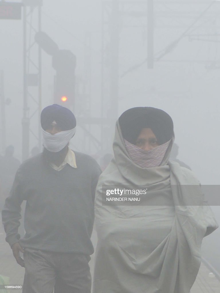 Indian passengers wait for their trains at a fog-covered railway station in Amritsar on December 24, 2012. Seasonal heavy fog and cold weather disturbed train, bus and air schedules in northern India as temperatures dipped towards freezing.