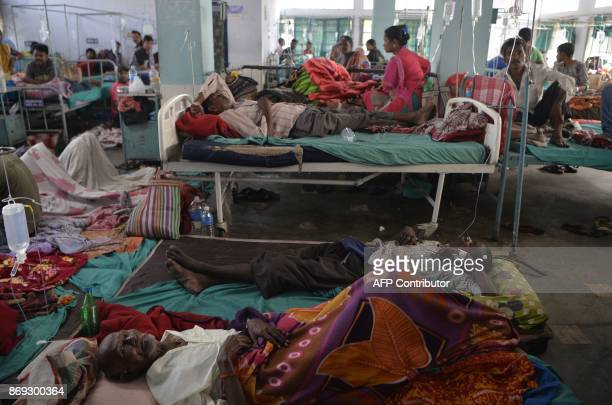 Indian patients undertaking treatment for viral infections including dengue fever lay on the floor in the overcrowded Siliguri District Hospital in...
