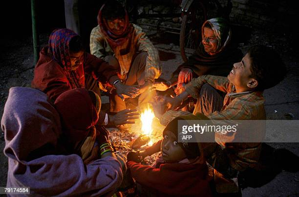 Indian pavement dwellers warm themselves around a fire in Siliguri 23 January 2008 as the temperature drops in the region At least 47 people have...