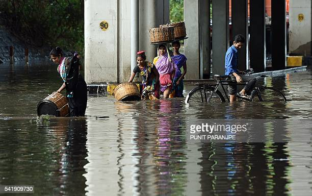 Indian pedestrians and a cyclist wade through a flooded street after heavy monsoon rain showers in Mumbai on June 21 2016 / AFP / PUNIT PARANJPE