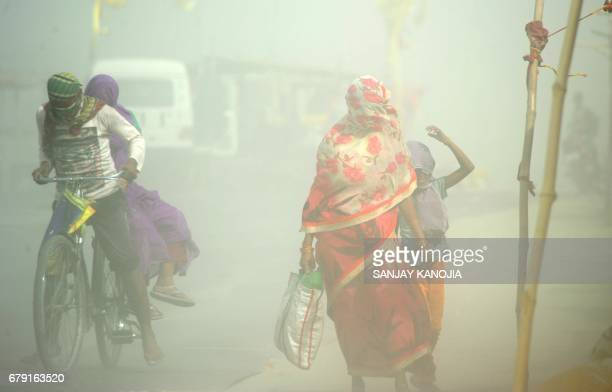 Indian pedestrians and cyclists travel through a dust storm at the Sangam the confluence of the rivers Ganges Yamuna and mythical Saraswati in...