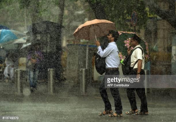TOPSHOT Indian pedestrians carry unbrellas as they walk through heavy rain showers in Mumbai on July 13 2017 / AFP PHOTO / PUNIT PARANJPE