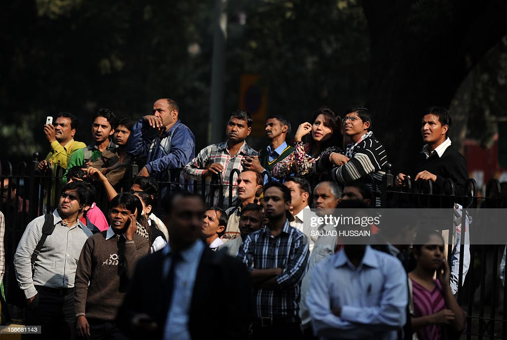 Indian pedestrians gather to watch as firefighters fight a blaze that broke out in a fifteen story building in New Delhi early November 19, 2012. No casualities were reported in the fire. AFP PHOTO/SAJJAD HUSSAIN