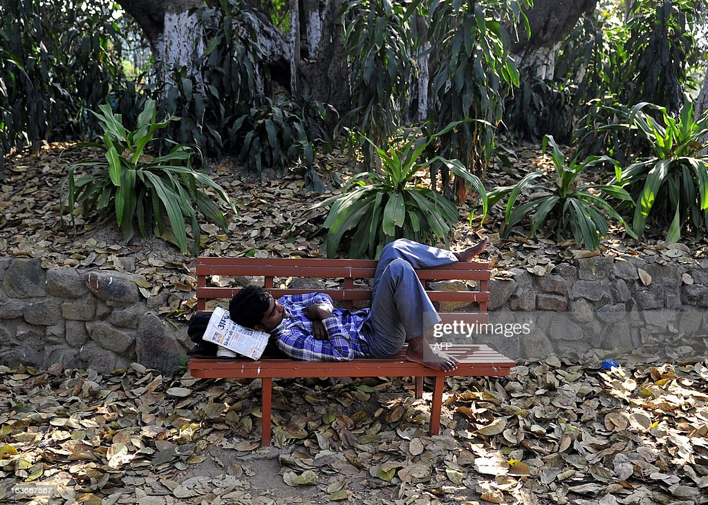 Indian pedestrians rest under the shade of trees at a park in Allahabad March 14, 2013. About 30 per cent of people in India were below the poverty line in 2009-10, based on the monthly per capita consumption expenditure (MPCE) in urban areas, Parliament was told in March 2013 by an expert panel.