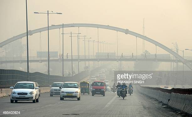 Indian pedestrians use a bridge to cross over motorists travelling on a major road as smog covers the capital's skyline in New Delhi on October 20...