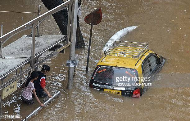 Indian pedestrians wade through a waterlogged neighbourhood in Mumbai on June 19 2015 Heavy monsoon showers lashed India's financial capital...