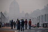 Indian pedestrians walk near smog enveloped government offices on Rajpath in New Delhi on December 1 2015 India's capital with 18 million residents...