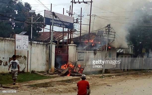 Indian pedestrians walk past a burning police station following violence in the Churachandpur district of the state of Manipur on September 1 2015...
