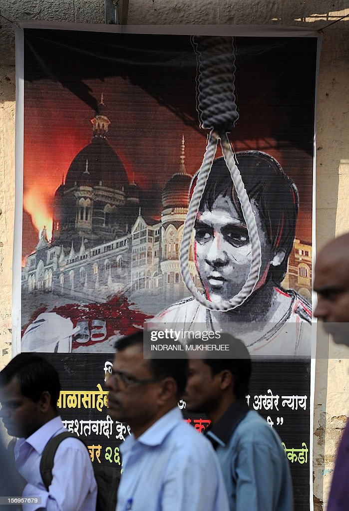 Indian pedestrians walk past a poster depicting the hanging of Pakistani-born Mohammed Ajmal Kasab, 25, the sole surviving gunman from the 2008 Mumbai attacks outside a railway station in Mumbai on November 26, 2012. A total of 166 people were killed and more than 300 others were injured when 10 heavily-armed Islamist militants stormed the city on November 26, 2008, attacking a number of sites, including the city's main railway station, two luxury hotels, a popular tourist restaurant and a Jewish centre.