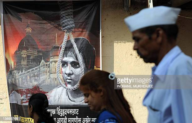 Indian pedestrians walk past a poster depicting the hanging of Pakistaniborn Mohammed Ajmal Kasab the sole surviving gunman from the 2008 Mumbai...