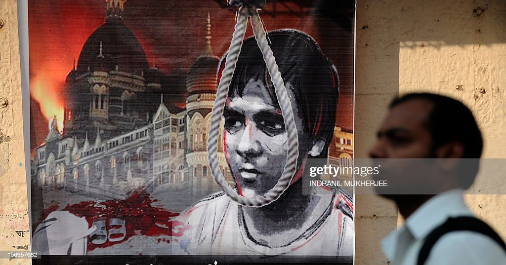 Indian pedestrians walk past a poster depicting the hanging of Pakistani-born Mohammed Ajmal Kasab, 25, the sole surviving gunman from the 2008 Mumbai attacks outside a railway station in Mumbai on November 26, 2012. A total of 166 people were killed and more than 300 others were injured when 10 heavily-armed Islamist militants stormed the city on November 26, 2008, attacking a number of sites, including the city's main railway station, two luxury hotels, a popular tourist restaurant and a Jewish centre. AFP PHOTO/ INDRANIL MUKHERJEE