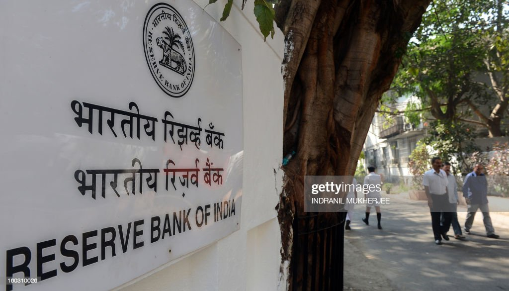 Indian pedestrians walk past a sign outside the Reserve Bank of India (RBI) headquarters in Mumbai on January 29, 2013. India's central bank cut its main interest rates by 25 basis points, in its first reduction for nine months as it seeks to kick start the slowing economy.
