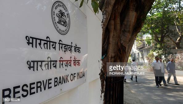 Indian pedestrians walk past a sign outside the Reserve Bank of India headquarters in Mumbai on January 29 2013 India's central bank cut its main...