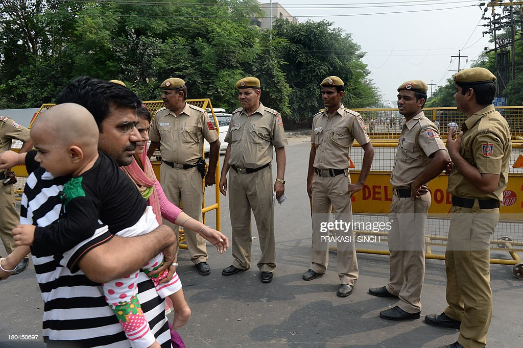 Indian pedestrians walk past police personnel standing guard outside the Saket Court Complex in New Delhi on September 13, 2013. The judge hearing the case of four men convicted for a shocking gang rape on a bus in New Delhi December 2012 sentenced them to death. AFP PHOTO/PRAKASH SINGH