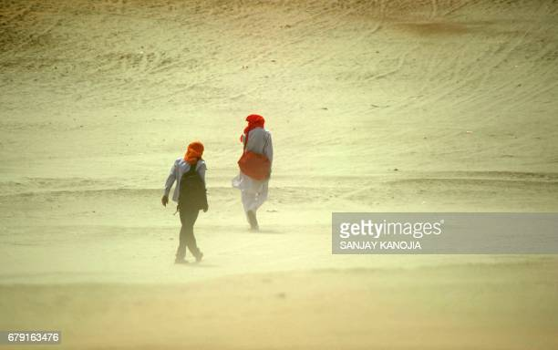 Indian pedestrians walk through a dust storm at the Sangam the confluence of the rivers Ganges Yamuna and mythical Saraswati in Allahabad on May 5...